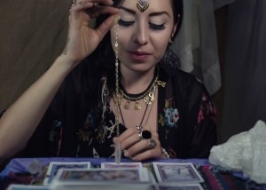Female psychic using a pendulum to read the tarot cards