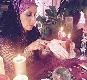 Female psychic pointing at her left hand for demonstrating palm readings
