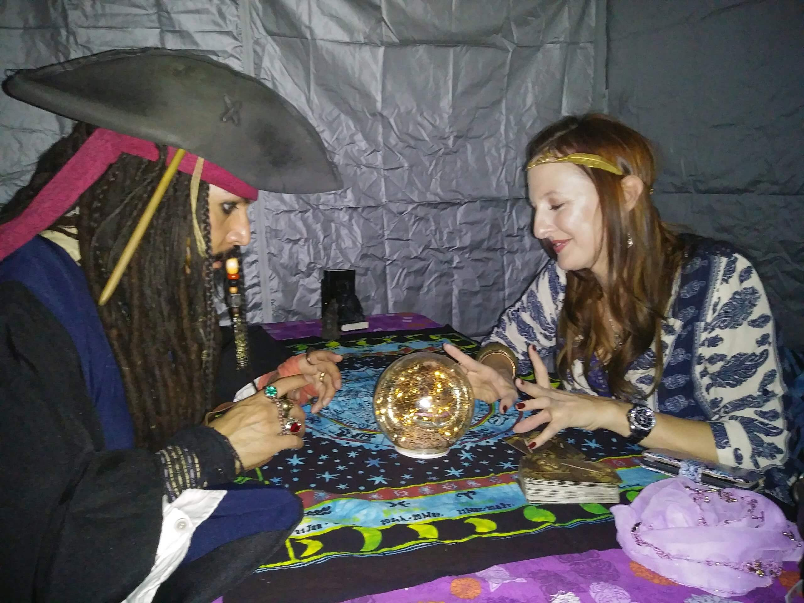 Female psychic performing Astrology to a client wearing a Jack Sparrow costume