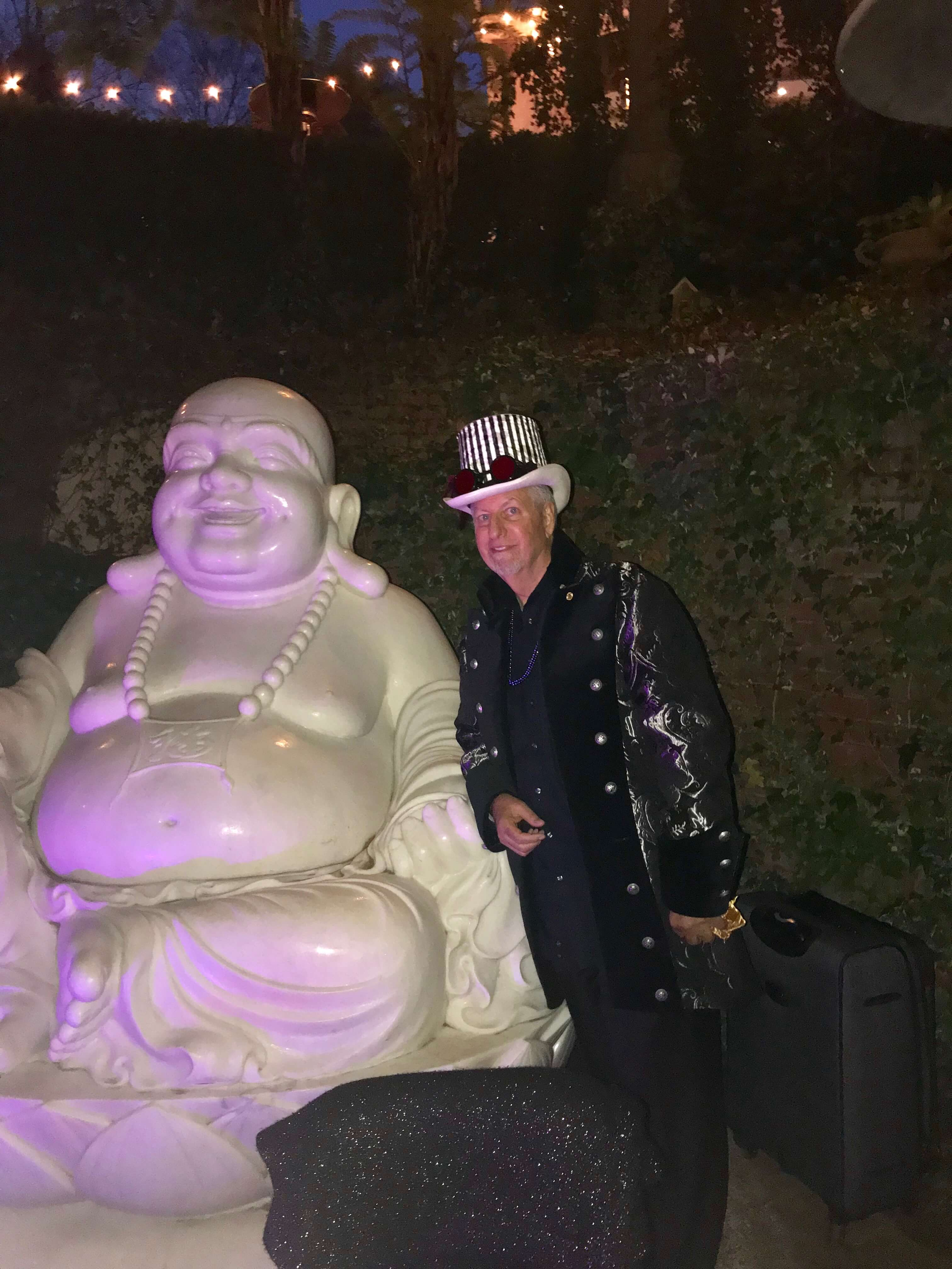 magician posing beside a fat laughing buddha statue