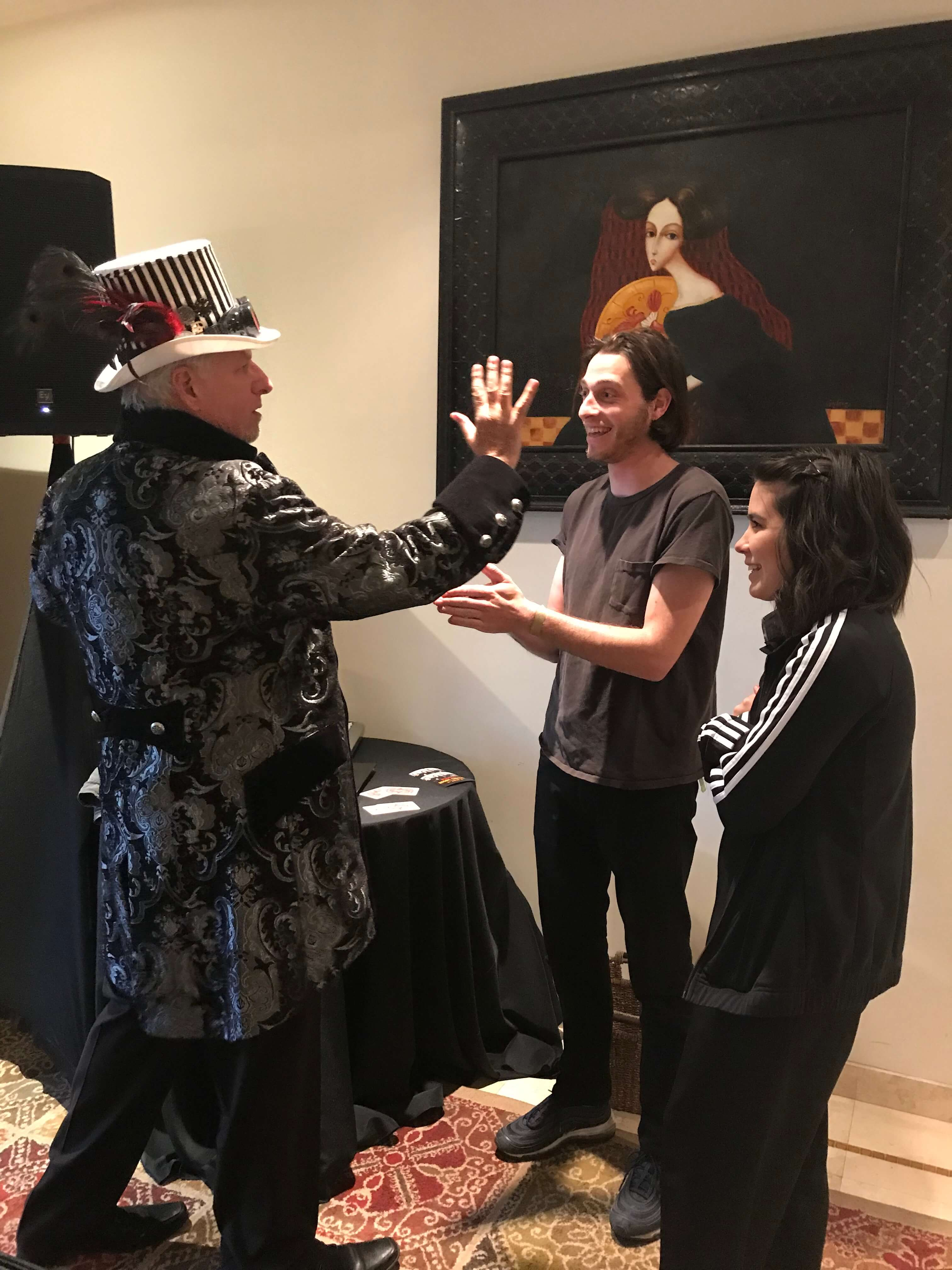 magician showing off his magic hand tricks to his two clients
