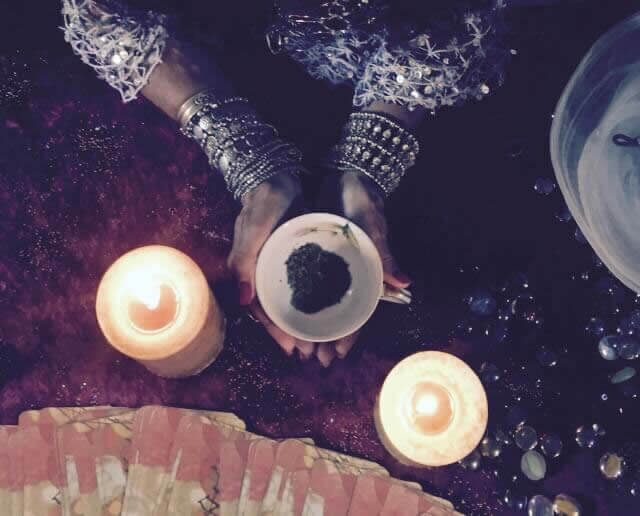 Psychic doing a tea leaf reading with two candles in between